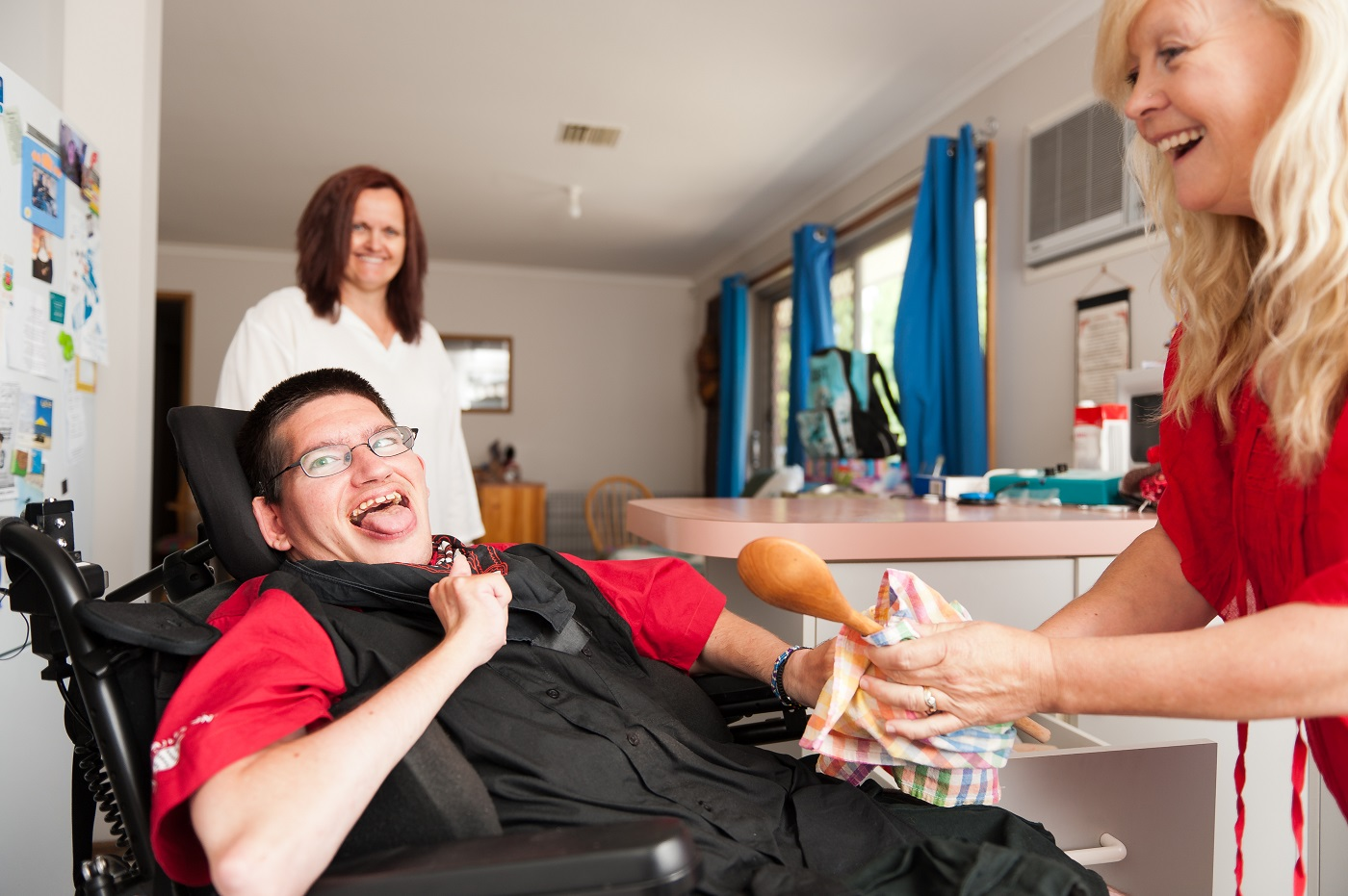 Young man with a neurological disorder being helped to wipe dry a wooden spoon.